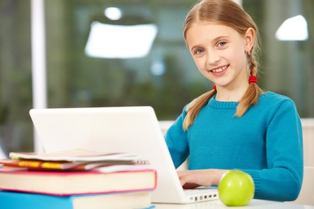 education technology: Portrait of smart schoolgirl sitting in classroom and typing