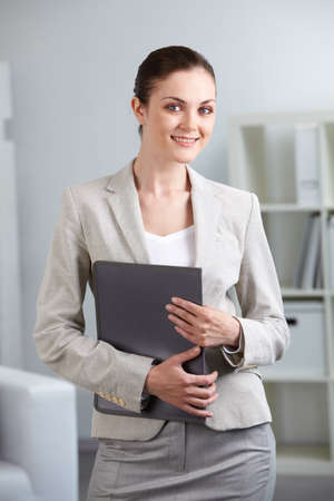 Portrait of smiling businesswoman with folder looking at camera in office photo