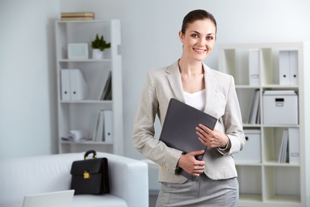 Portrait of smiling businesswoman with folder looking at camera in office Stock Photo - 9820142