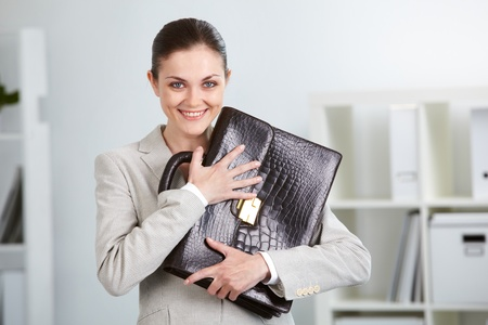 Portrait of smiling businesswoman with briefcase looking at camera in office Stock Photo - 9819817