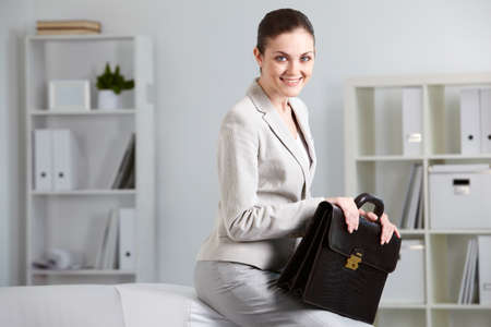 Portrait of smiling businesswoman with briefcase looking at camera in office Stock Photo - 9819734