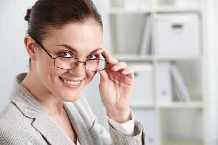 Portrait of successful businesswoman looking at camera through eyeglasses photo