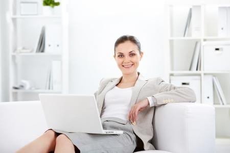mujeres sentadas: Retrato de empresaria sonriente con port�til mirando la c�mara en la Oficina