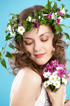 Beautiful woman in floral wreath looking aside photo
