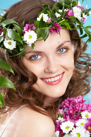 Beautiful woman in floral wreath looking at camera with smile photo