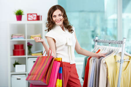 Portrait of pretty woman with colorful bags looking at camera in clothing department photo