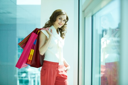 Portrait of happy girl with paper bags looking at camera in the mall Stock Photo - 9819902