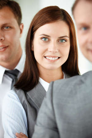 Portrait of pretty woman looking at camera between employees photo