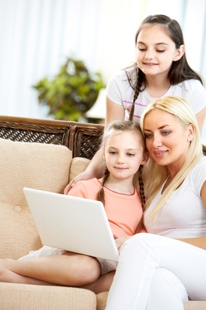 Pretty woman and her two daughters sitting on sofa and looking at laptop screen  photo