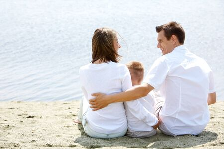 Backs of happy family sitting on sandy shore in front of blue water Stock Photo - 9817843