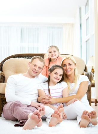 Portrait of happy family with two children sitting at home  photo
