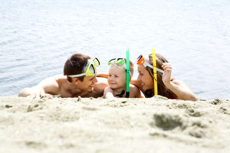 Portrait of cheerful couple and their son in diving equipment lying on sandy shore photo