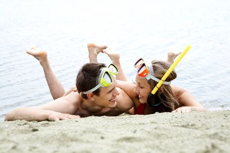 Portrait of cheerful couple in diving equipment lying on sandy shore photo