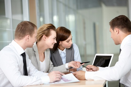 A business team of four sitting at table and planning work photo