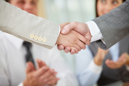 Photo of handshake of business partners on background of two partners applauding photo