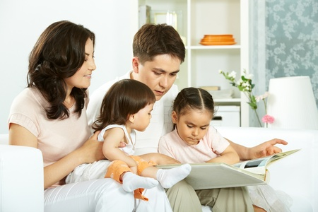Portrait of happy family with two children sitting at home and reading book Stock Photo - 9819579