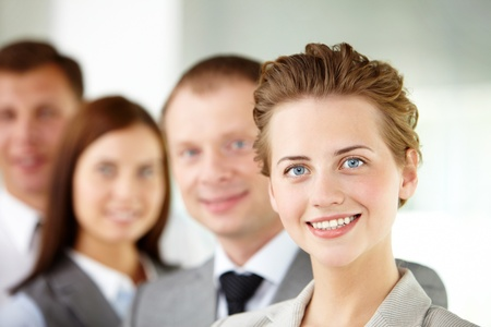leaders: Portrait of friendly leader looking at camera with three employees behind