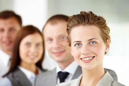 lideres: Retrato del l�der amistoso mirando la c�mara con tres empleados detr�s Foto de archivo