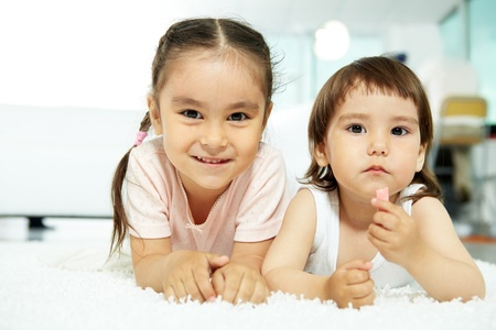 Portrait of happy girl looking at camera and smiling with her sister near by Stock Photo - 9817833
