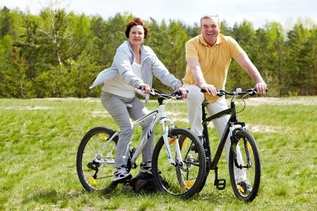 pareja madura feliz: Retrato de la feliz pareja madura en bicicletas