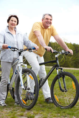 pareja madura feliz: Retrato de una pareja madura feliz en bicicleta