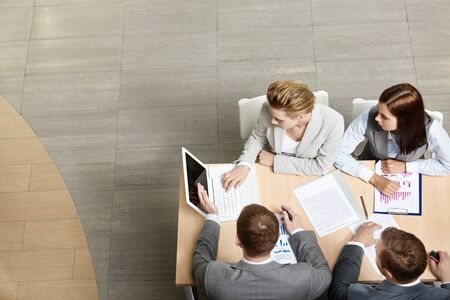 consulting team: Image of business partners sitting at table and planning work