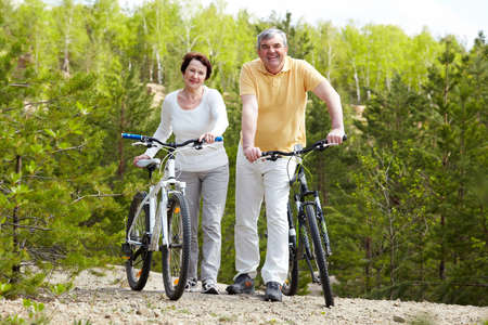 Portrait of happy mature couple with bicycles looking at camera photo