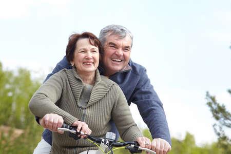 pareja madura feliz: Retrato de la feliz pareja madura en bicicleta junto  Foto de archivo