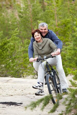 Portrait of happy mature couple riding bicycle photo