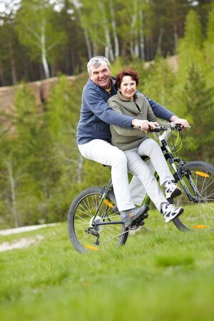 Portrait of happy mature couple on bicycle outdoors photo