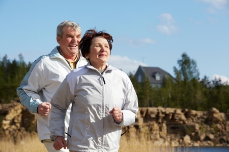 Portrait of happy mature couple running together  photo