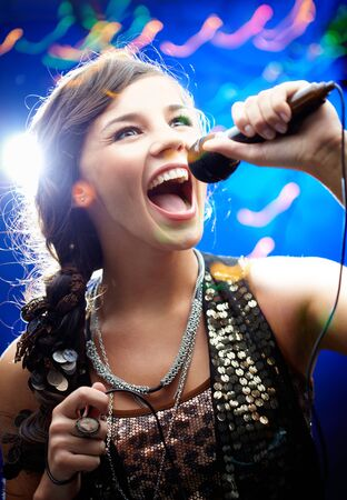 stage performer: Portrait of a glamorous girl holding a mike and singing   Stock Photo