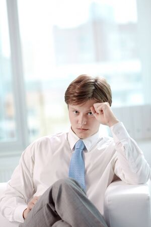 Image of young serious businessman sitting in office and looking at camera photo