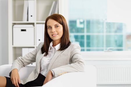 Portrait of smiling businesswoman looking at camera while sitting in office photo