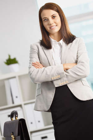 Portrait of smiling businesswoman with briefcase looking at camera Stock Photo - 9819346