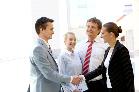 Portrait of two business partners handshaking after making agreement with two employees near by Stock Photo - 9819363
