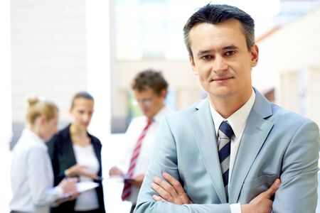 Portrait of attractive male in suit looking at camera with communicating associates on background photo