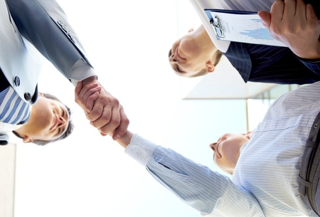 Below angle of successful associates handshaking after striking deal photo