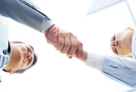 Below angle of successful associates handshaking after striking deal Stock Photo - 9819442