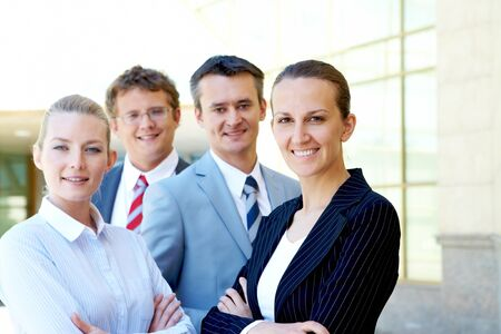 Portrait of friendly female looking at camera with several employees near by Stock Photo - 9817986