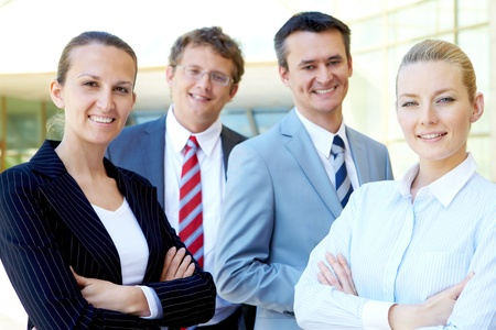 friendly people: Portrait of friendly female looking at camera with several employees near by Stock Photo