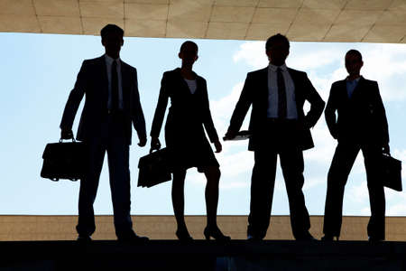 Silhouettes of several business partners standing in row outside photo