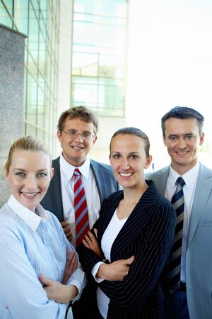 Group of confident business partners looking at camera outside photo