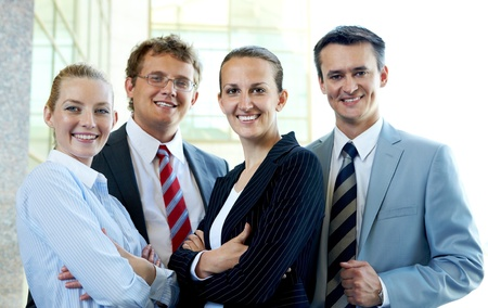 competitive business: Group of confident business partners looking at camera with smiles Stock Photo