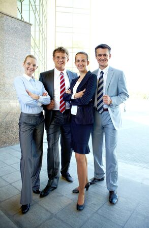 Group of smart business partners looking at camera outside photo