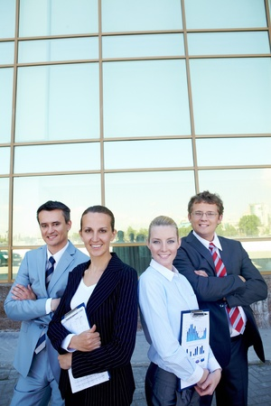 Group of confident employees with documents looking at camera outside photo