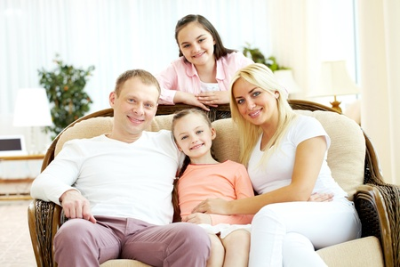 Portrait of happy family with two children sitting at home Stock Photo - 9819275