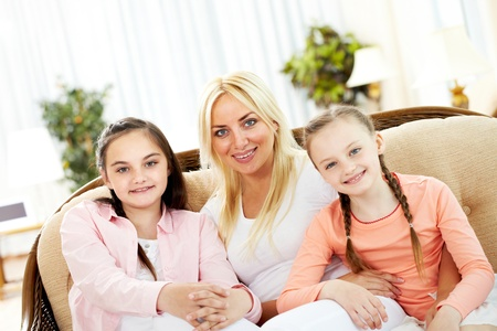 Portrait of happy mother and two daughters sitting on sofa Stock Photo - 9819126