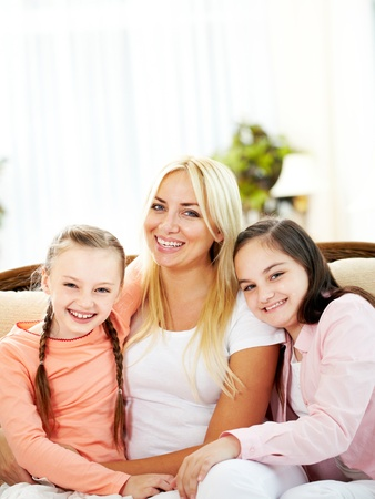 Portrait of happy mother and two daughters laughing while looking at camera Stock Photo - 9818886