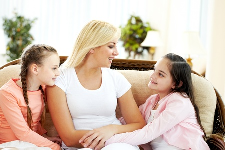 children talking: Portrait of happy mother and two daughters communicating at home